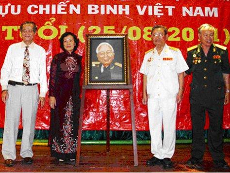 """Đại tá Hoàng Minh Phương (thứ hai từ bên phải qua) trao bức """"Hào khí trăm năm"""" do nghệ nhân Ý Lan gửi tặng cho Đại tướng. Ảnh: Tá Lâm."""