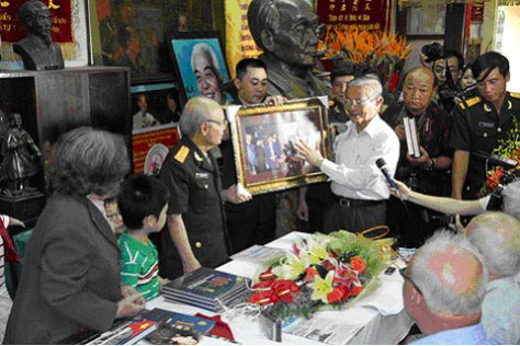 Giáo sư Phan Huy Lê tặng gia đình Đại tướng bức ảnh ông chụp chung với Hội sử học Việt Nam. Ảnh: Nguyễn Hưng/báo vnexpress