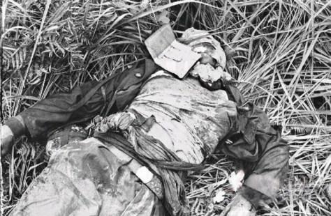Ngày 23/02/1979. Một dân quân tử trận nằm kế bên mộ tập thể của 62 Bộ đội Việt Nam tử trận tại Vị Xuyên, trên Quốc lộ 2C. Nguồn ảnh: Hoa Chí Cường.
