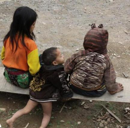 Cha mẹ lao động ngoài nương rẫy để con em tự ngồi dưới đất chơi với nhau, quanh năm như một ngày. Cái tuổi này mai sau không khá hơn cha mẹ. Các em sinh ra trong dòng đời tị nạn, cứ thế kéo lê thê đã bao năm. Ảnh: Nhất Biến.