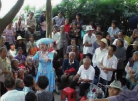 Người dân Tây Hành làng tụ thập trước nhà làng để nghe tin vui và giới thiệu những người bạn của làng. Ảnh: Nhất Biến.