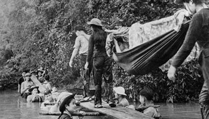 Đại đội TNXP 20/12 miền Nam lấy thân mình làm trụ cầu để đồng đội tải thương binh. (Ảnh tư liệu Bảo tàng Lịch sử Quốc gia cộng sản.)