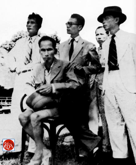 Phạm Văn Đồng (t), Võ Nguyên Giáp (p) bên cạnh Hồ Chí Minh ngồi ghế mặc veston, quần ngắn, đi dép râu (Mùa Thu 1945). Nguồn: Triumph Forsaken.