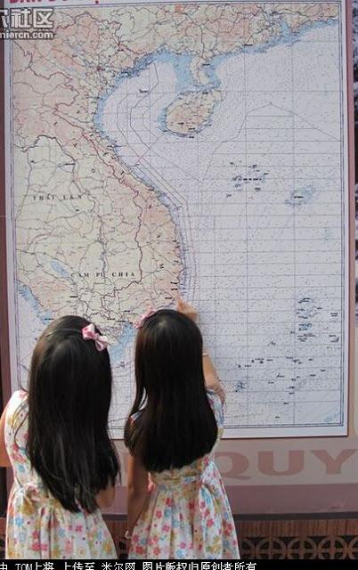 Hai em bé gái Việt Nam nhìn vào phiên bản đồ tiếng Việt Nam, chỉ vào điểm biển Việt Nam thu hẹp. Trung Quốc vẽ một đường bản đồ đại diện cho tham vọng cướp Biển Đông. Nguồn: Tài liệu ảnh lưu: Huỳnh Tâm.